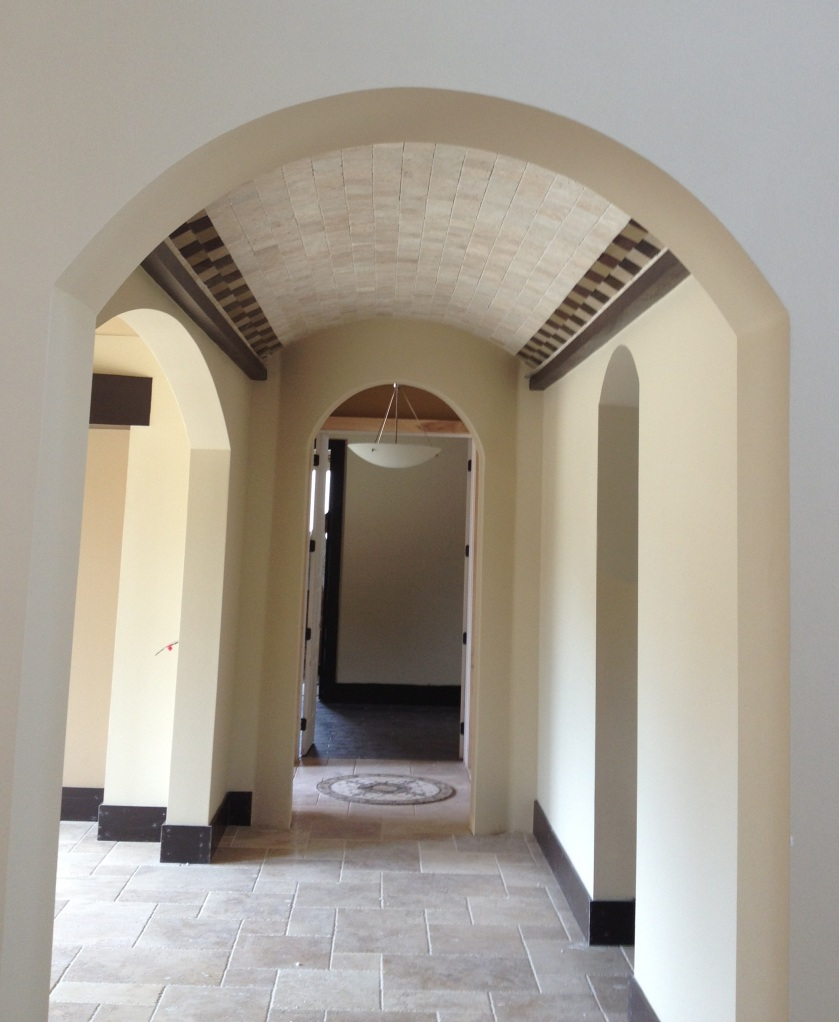 A Mod-Mediterranean style barrel ceiling. Notice how glass tiles in earth tones edge the rustic travertine tiles for a seamless blend of Old World and Modern. This hallway is in a Mod-Mediterranean home under construction by Orlando Custom Home Builder Jorge Ulibarri.